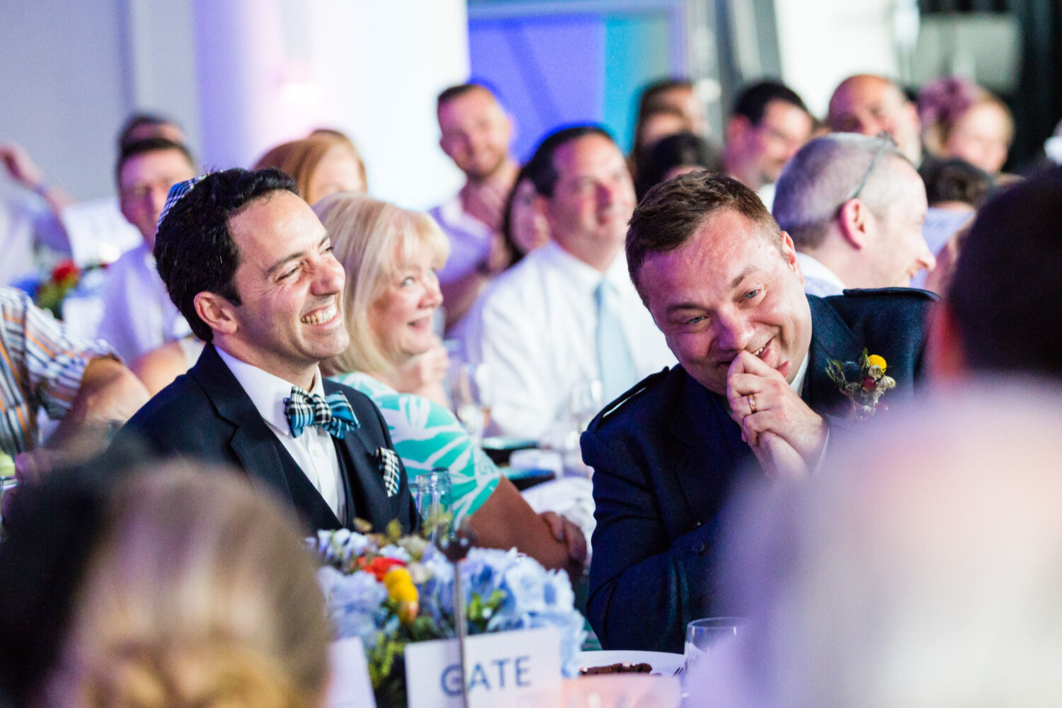 Two groom laugh at their wedding day speeches
