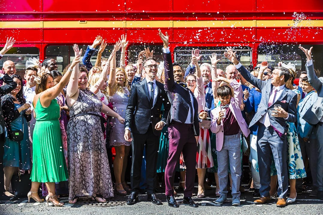 confetti thrown in front of a london red bus during a same sex wedding in london