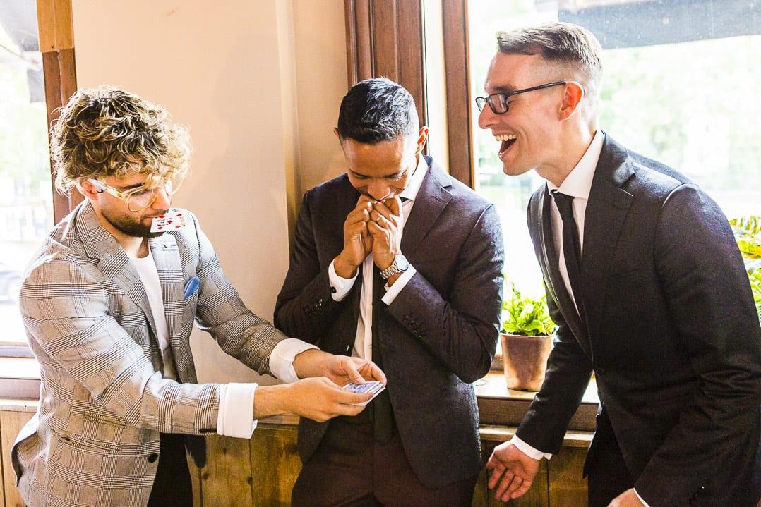 two grooms react ot a magic trick o their wedding day