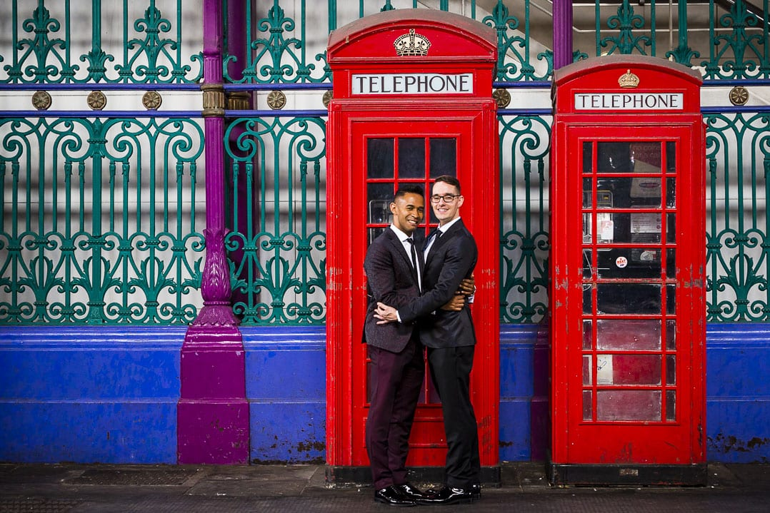two grooms pose in front of two red telephone boxes in smithfield market