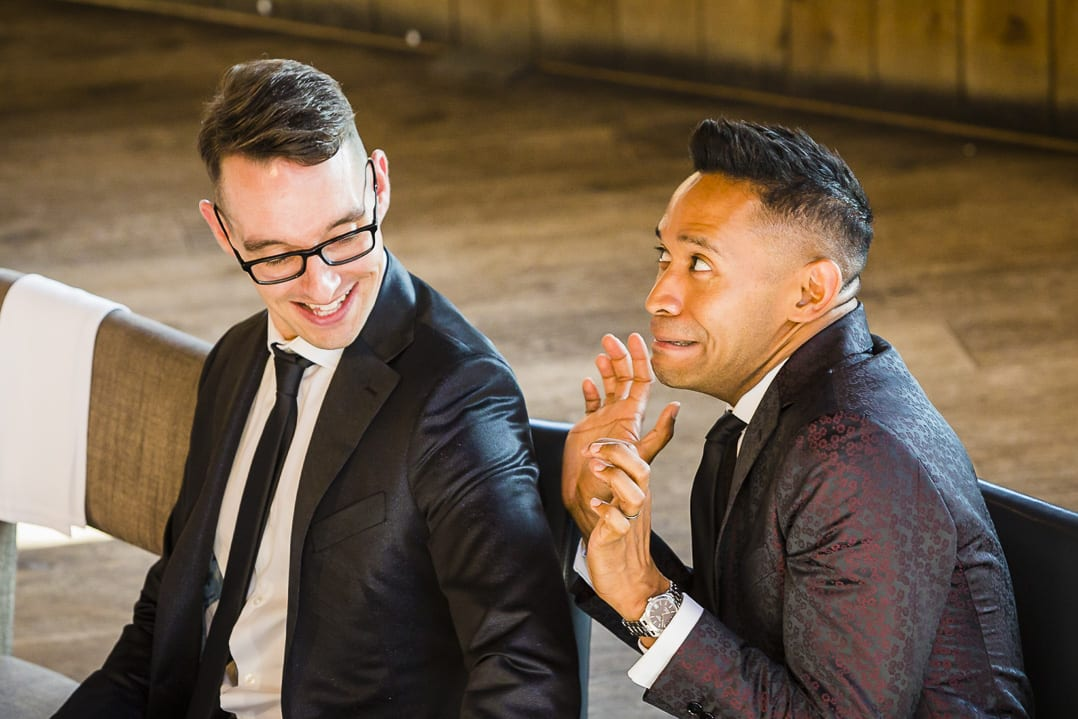 a groom pulls a silly face during the wedding speeches at his gay wedding