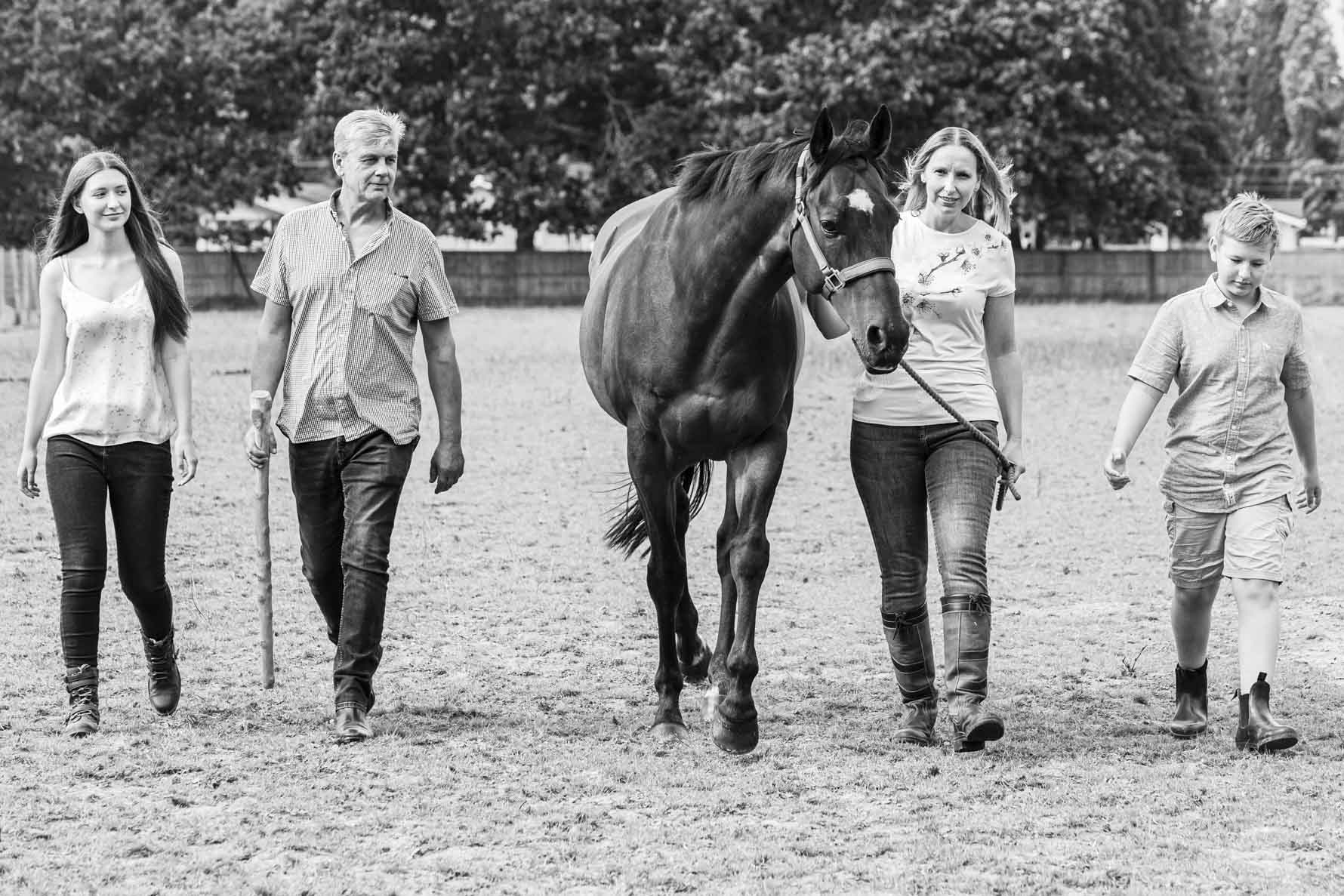 A family of four walk towards the camera leading their horse in the centre