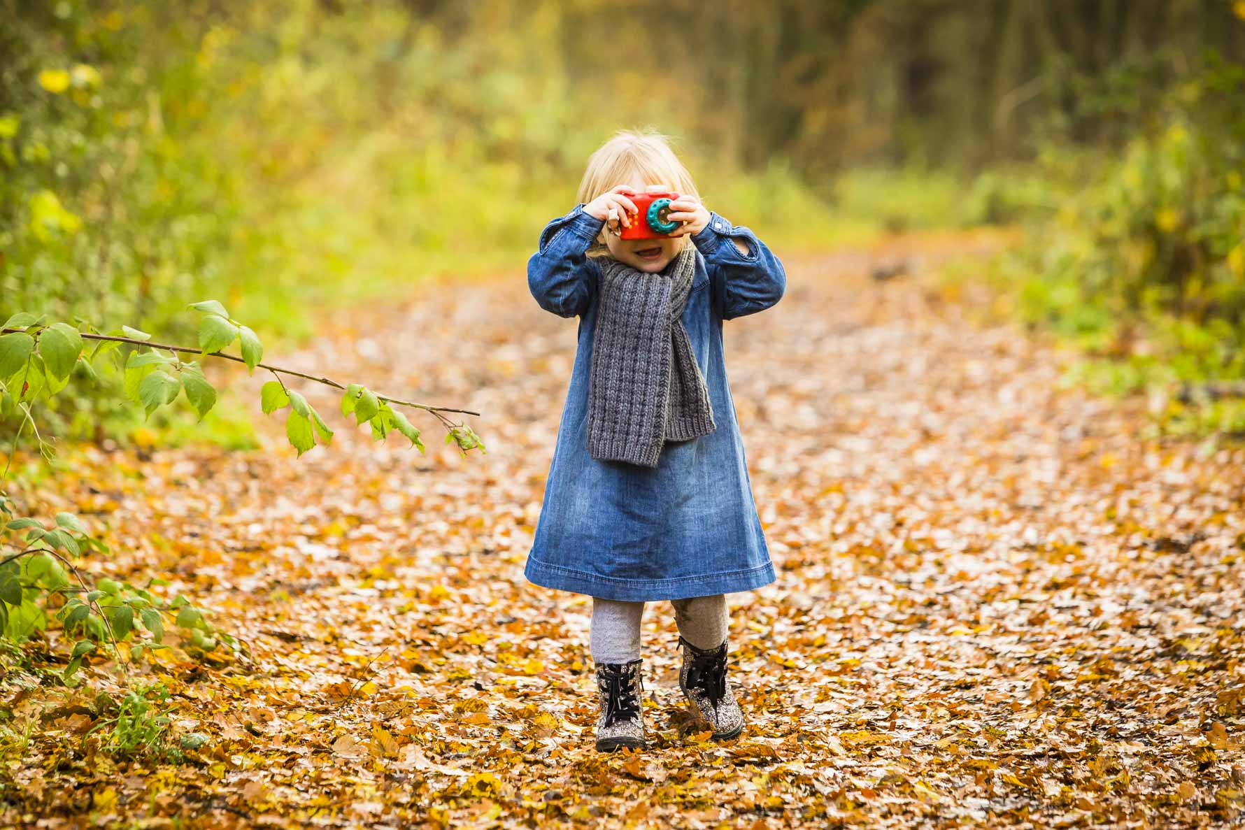 a girl takes a photo of the person taking this photo as she walks through the woods in autumn