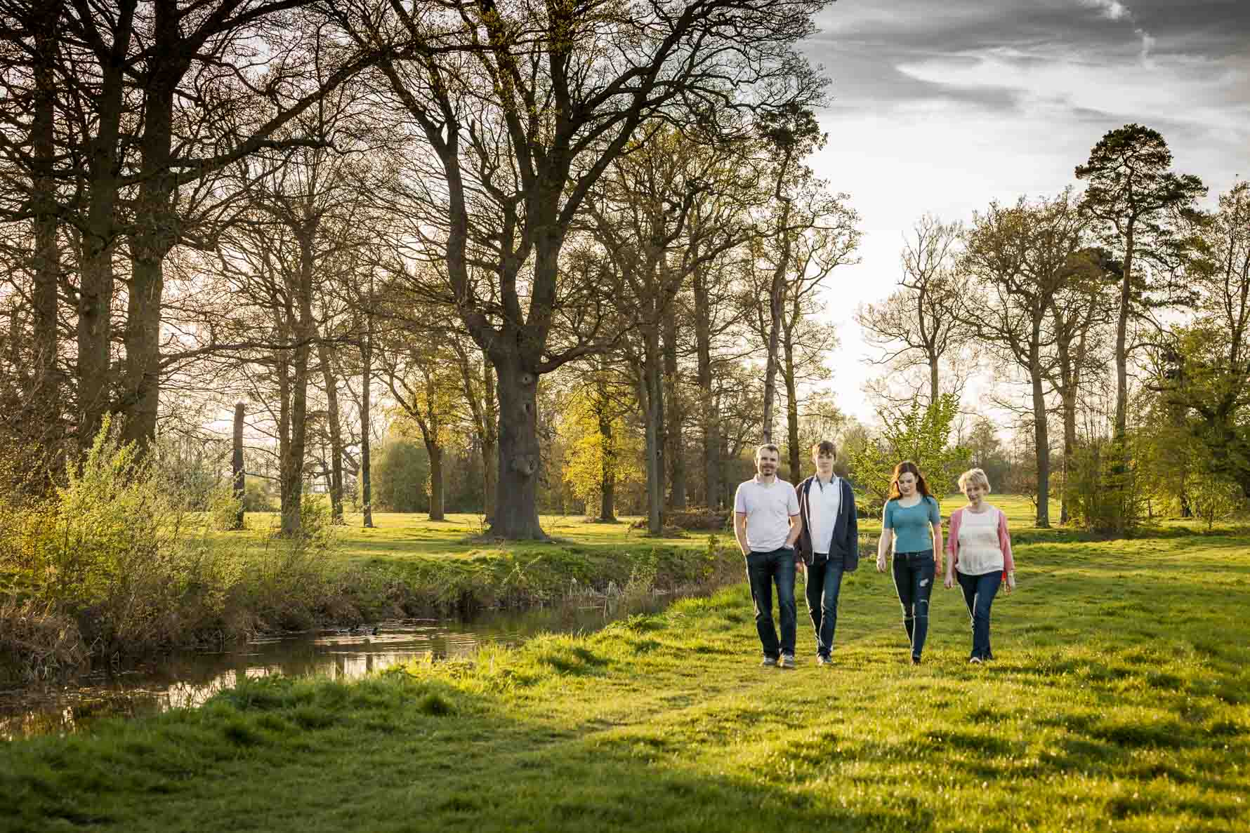 A family of four walk by a lake in the golden hour