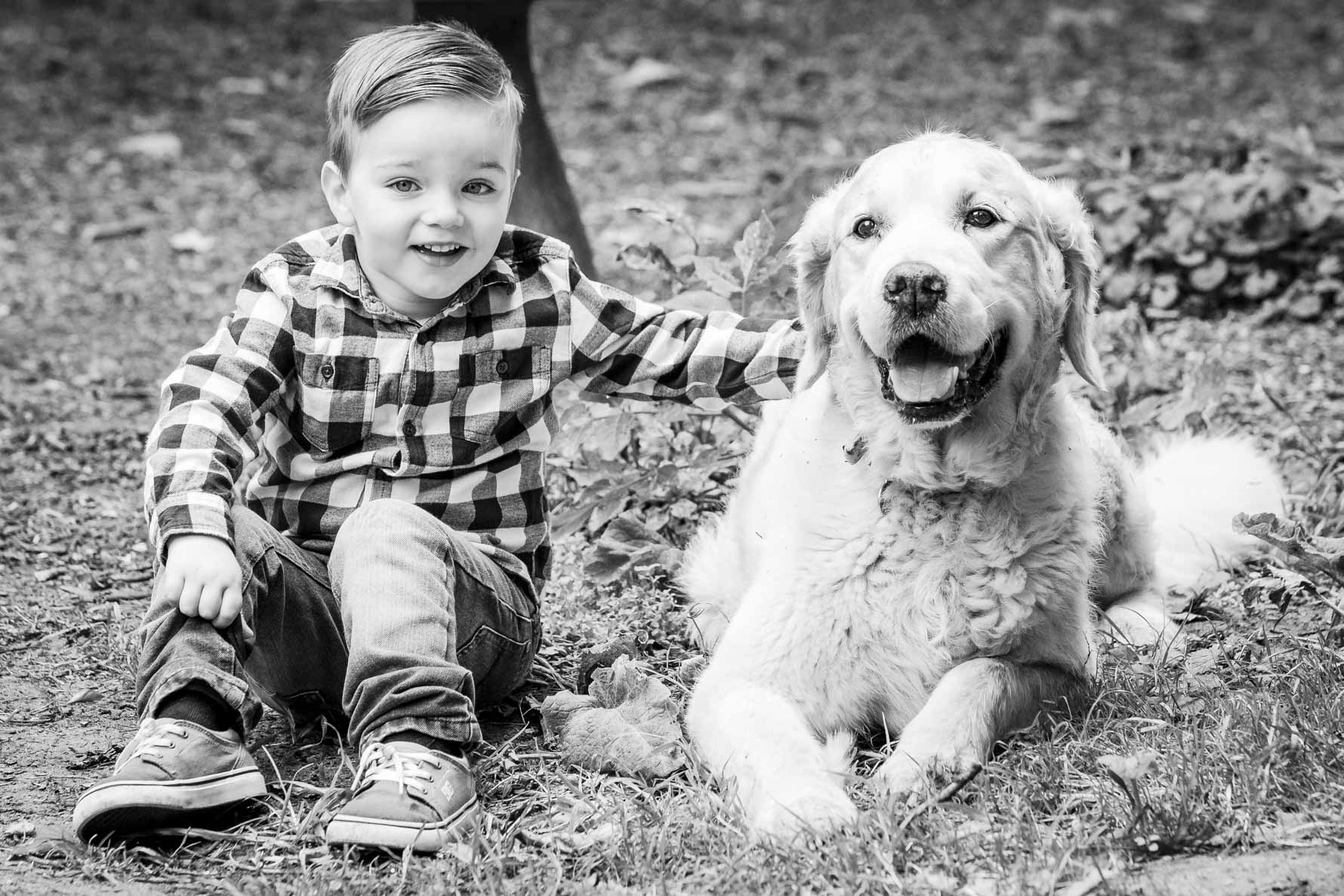 a boy sat next to a dog photographed n clack and white
