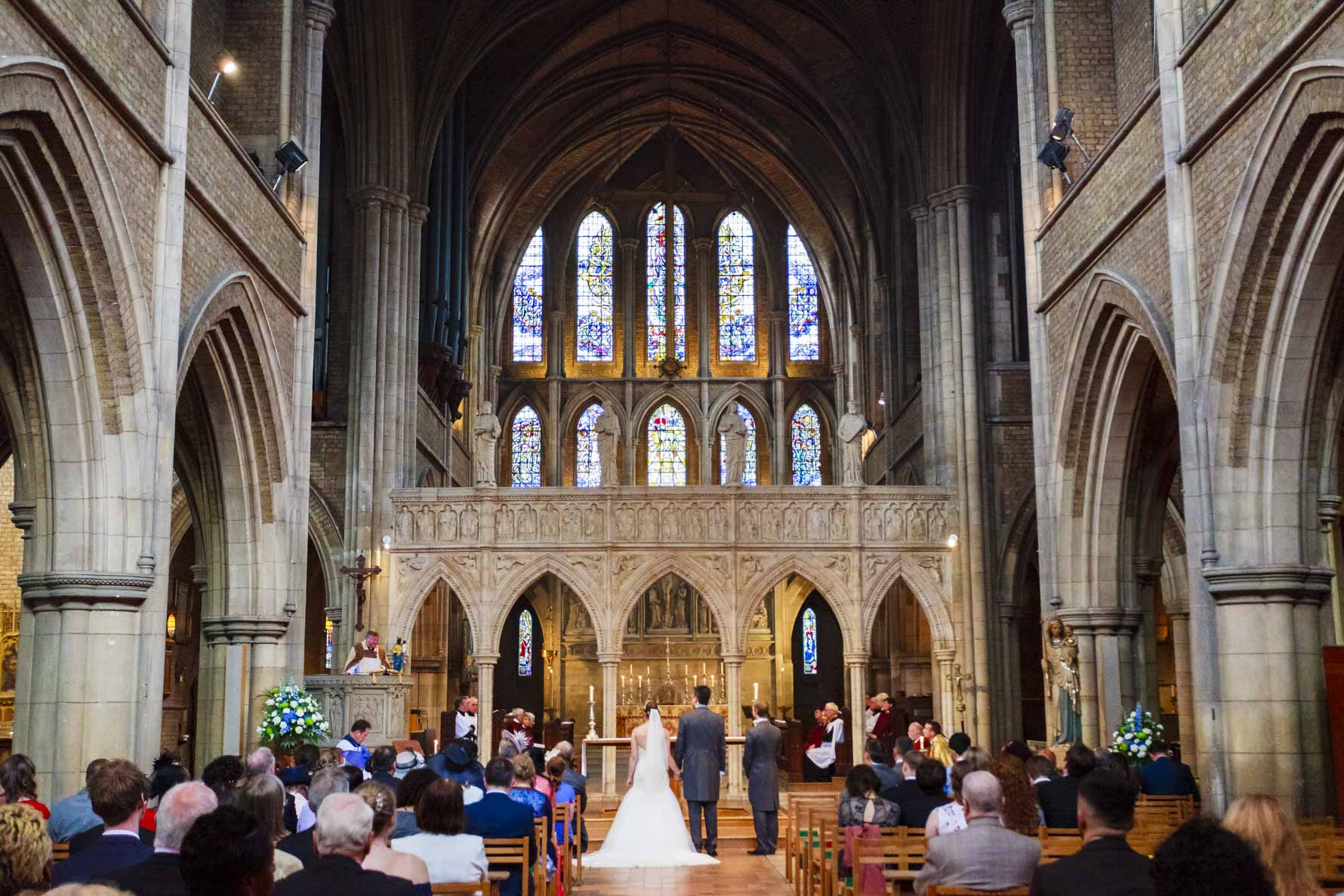 A wdie angle shot of a couple in church on their wedding in front of a huge stained glass window