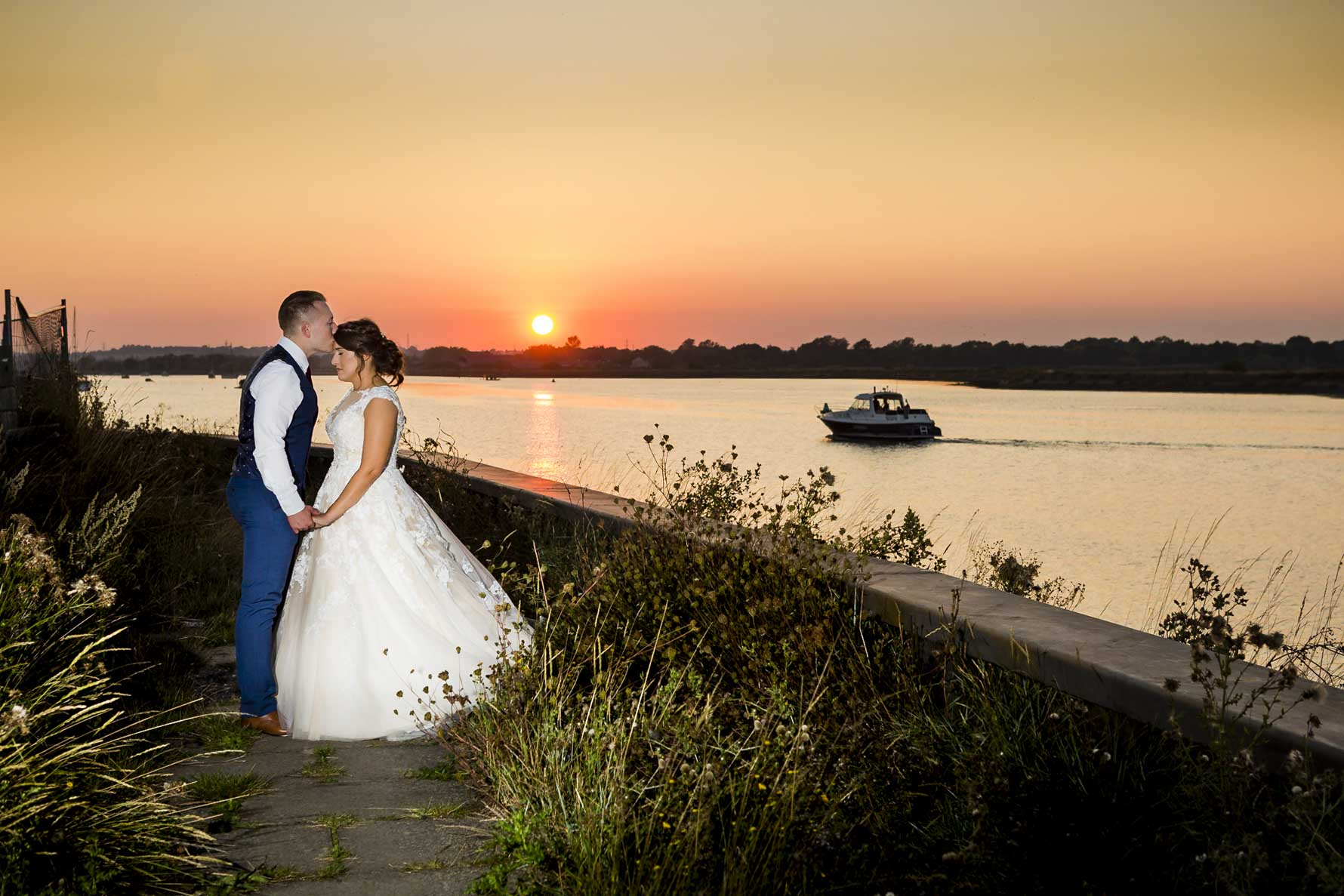 A bride and groom embrace net ot a river under a setting sun