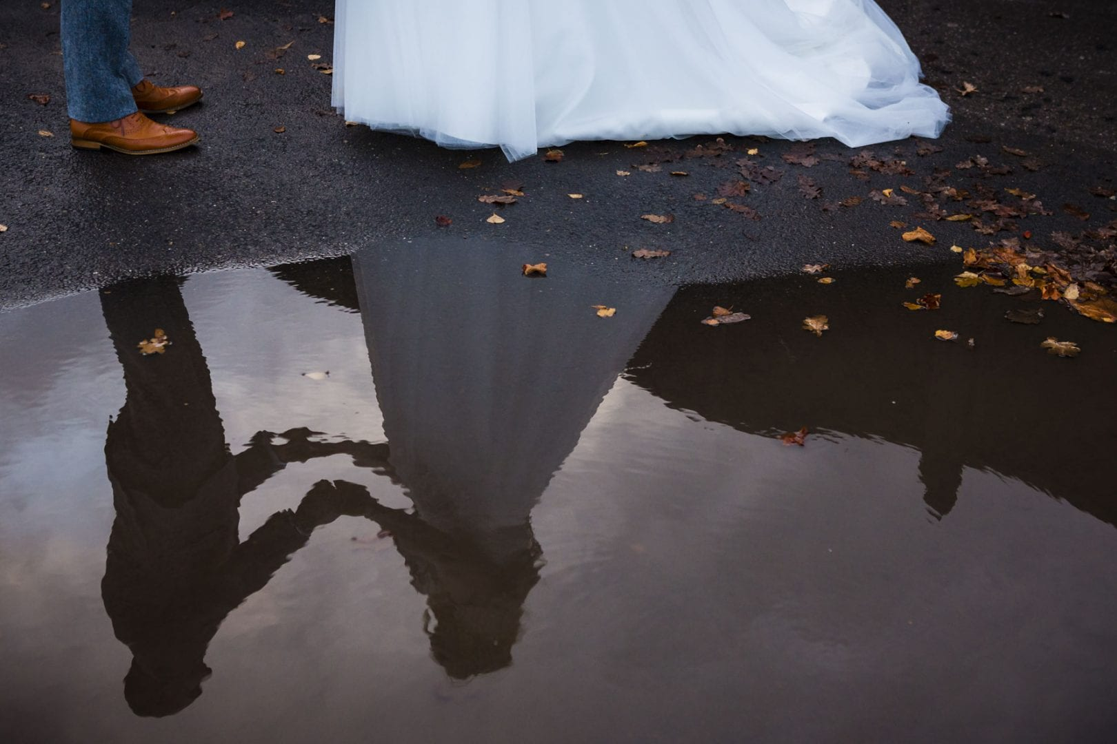 A reflection of a bride and grooming s puddle
