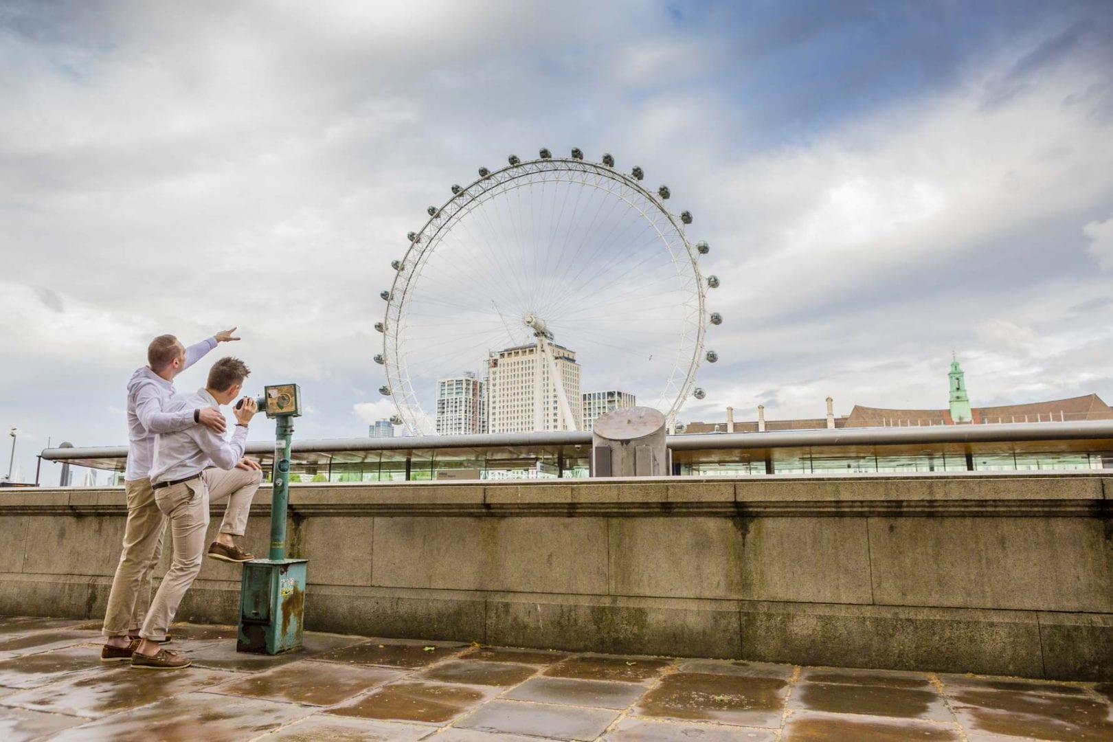 Two grooms look out to the London Eye on their pre-wedding shoot