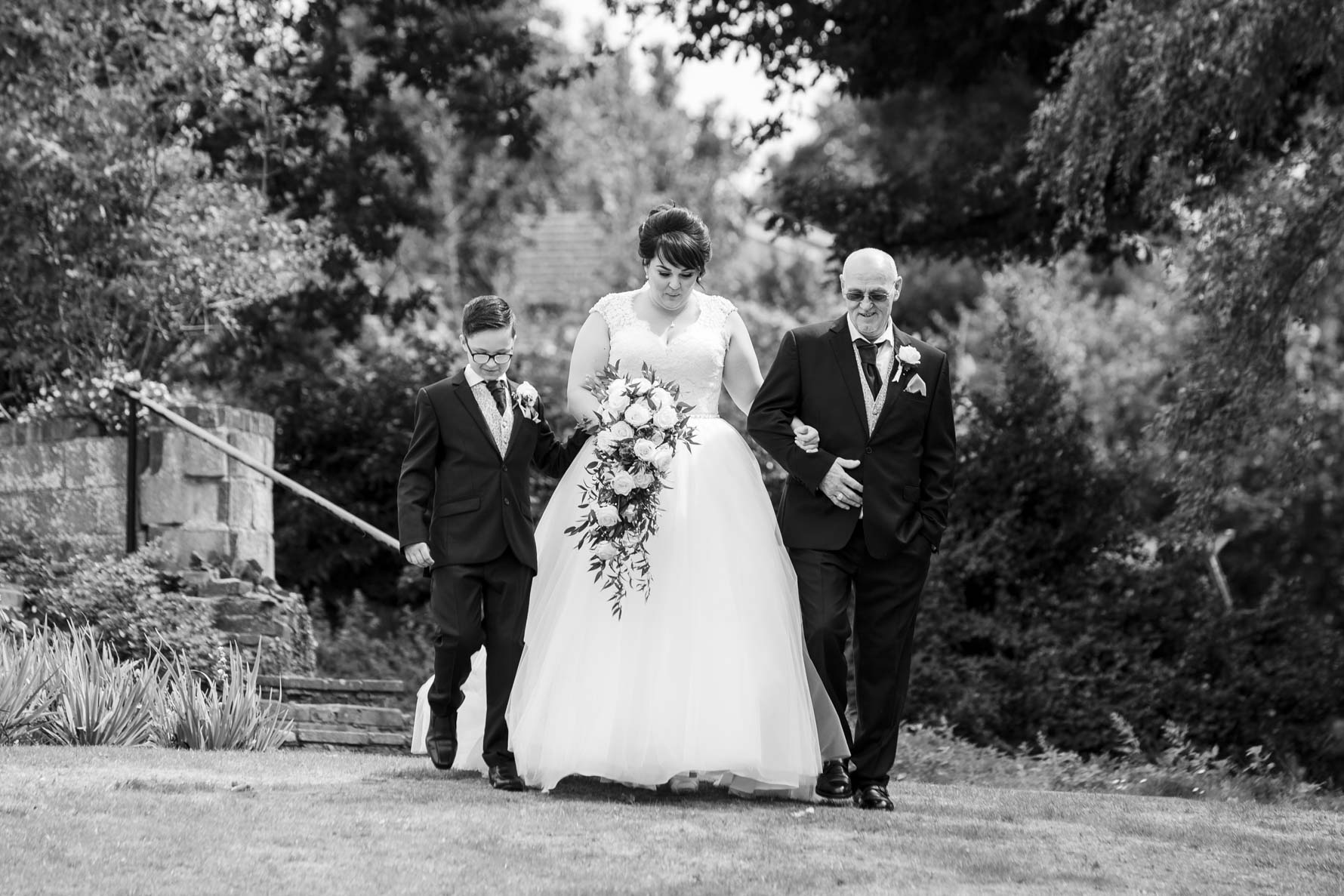 A bride walks to her wedding ceremony with her son and her father either side